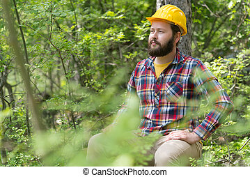 a bearded chainsaw worker in the forest