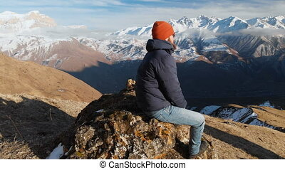 A bearded hipster in sunglasses is sitting on a large stone on a hillside against the background of snow-capped mountains. Travel video aerial view