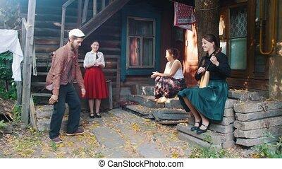 A bearded man dancing russian folk dance - women sitting on...