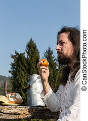 bearded man eating an apple in the nature