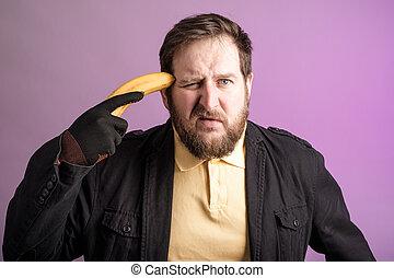 a bearded man held a banana to his head like a pistol