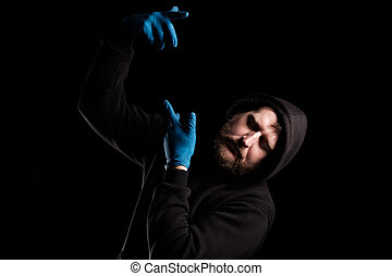 a bearded man in a hood made a figure with his hands, there is nothing in his hands