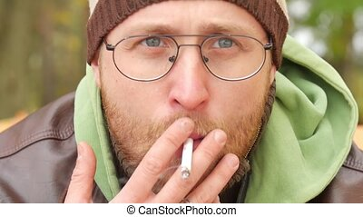 A bearded man in a sweater and leather jacket in the fall on a bench smoking a cigarette exhaling smoke