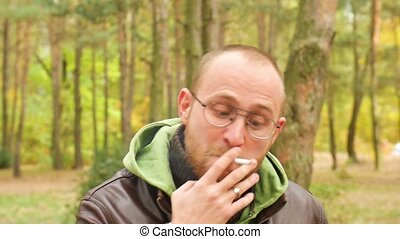 A bearded man in a sweater and leather jacket in the fall Yelling and swearing with an angry face at the viewer smoking a cigarette exhaling smoke into the chamber in slow motion