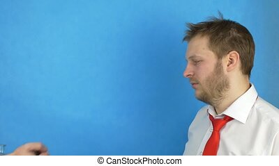 A bearded man in a white shirt and tie holds on to the head of the problem, and buys alcohol for money, blue background, intermediary