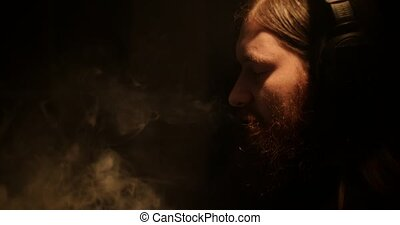 A bearded man in the darkness smokes an electronic cigarette and listens to music
