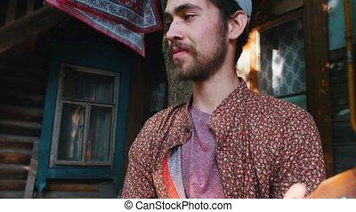 A bearded man playing balalaika outdoors - sitting on the...