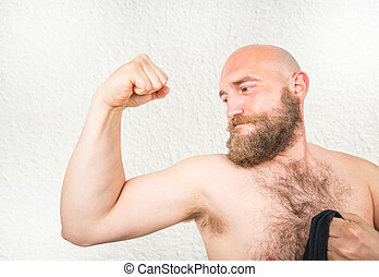 a bearded man showing his arms muscle