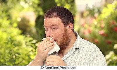 A bearded man suffers from pollen