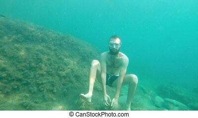 A bearded man without underwater equipment underwater pretends to meditate in the sea. Slow motion