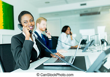 A beautiful, black, young woman working at a call center in an office with her red haird partner on the other end of the desk