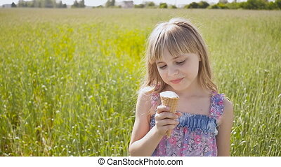 A beautiful blond girl eats an ice cream in the summer next to a wheat field and runs off into the distance. Warm sunny day.