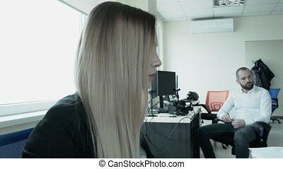 A beautiful blonde in the office turns on her chair and stares in front of her. Close-up of a painted young woman. The camera approaches the face.