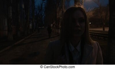 A beautiful blonde is walking along a dark street at night. Close-up of a walking young woman.
