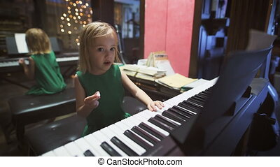 Happy childhood. A cute little girl is playing piano. A pretty blondie is playing piano and eating some sweets.