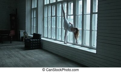 A beautiful blonde with flowing hair is standing on the windowsill and raises her legs in a graceful dance. A young woman in a pose with a raised foot as a ballerina is standing on a large window.