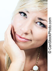 A Beautiful blonde woman posing standing facing the camera.