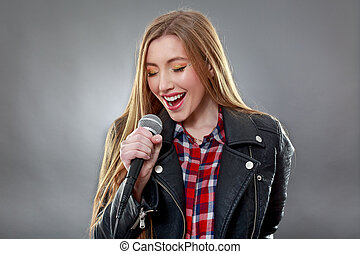 a beautiful blonde woman singing in microphone