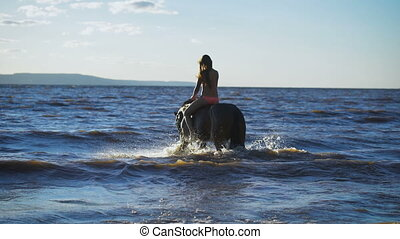 A beautiful blonde young sexy woman in a red dress riding a horse at a lake.