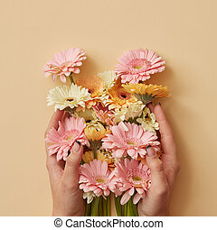 A beautiful bouquet of gerbera the girl is holding in hands on a yellow paper background.