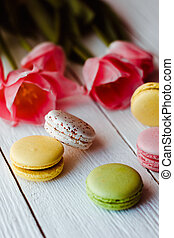 A beautiful bouquet of pink tulips with colorful macaroons on white wooden background