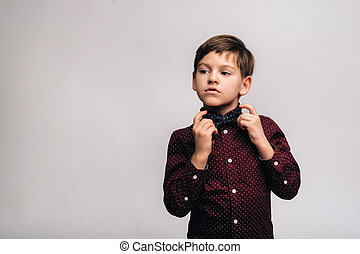 A beautiful boy in a shirt and bow tie stands on a gray background