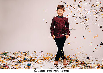 A beautiful boy stands and confetti falls on him on a gray background