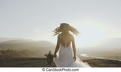A beautiful bride in a white dress circles around herself in the mountains in the sunset on the background of the river and the coniferous forest
