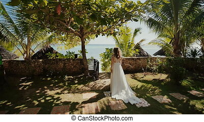 A beautiful bride in a white long wedding dress walks along a path among the palm trees to the groom. Solemn moment. The groom is waiting under the arch. A tropical wedding.