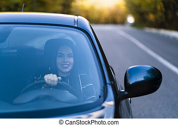 A beautiful brunette driver smiles in her new car
