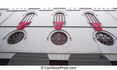 A beautiful building of Spanish architecture with waving red flags on the facade. Large windows of a religious structure.