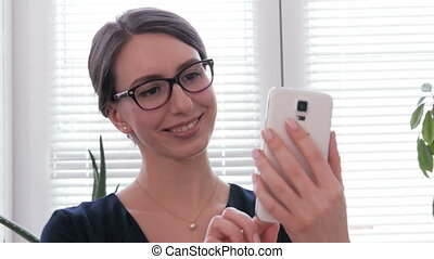 A beautiful businesswoman using phone and smiling for a selfie