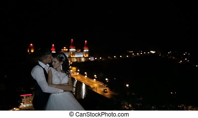 A beautiful castle on a hill. Fortified palace on the rocks at night. Towers with a red-blue backlight. The couple kisses against the background of the castle.