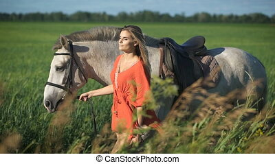 A beautiful charming blonde woman walking with a horse at a field