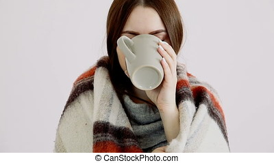 a beautiful cold girl of Eurarean appearance in a woolen blanket is drinking hot tea by the white wall.