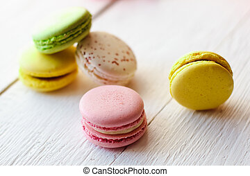 A beautiful colorful macaroons on white wooden background