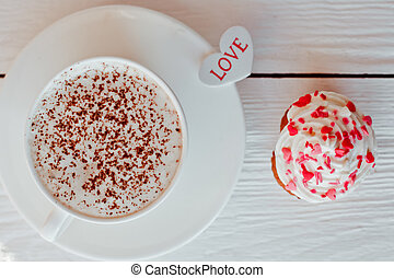 A beautiful Cup of coffee with a muffin on white wooden background