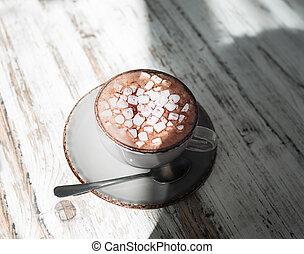 A beautiful cup of milk coffee with marshmallows on a gray wooden background. A cocoa drink in a porcelain cup.