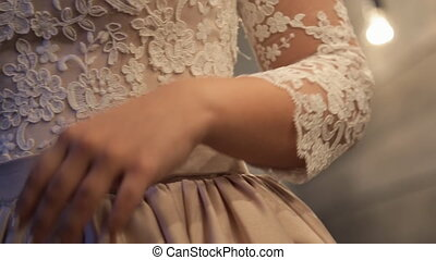 A beautiful dress with a belt is decorated with a lace of beige color.