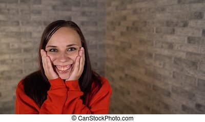 A beautiful emotional woman in a red hoodie is happily ...