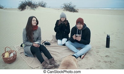 A beautiful family arranged a picnic on the beach with dogs.
