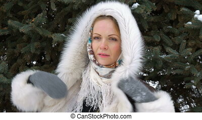 A Beautiful Fashion Model Smiling and Looking At Camera. Drifting snow in the winter. Close-up