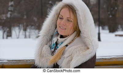 A Beautiful Fashion Model Smiling and Looking At Camera. Drifting snow in the winter