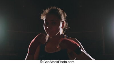 A beautiful female boxer strikes directly into the camera...