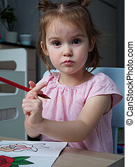A beautiful girl 4-5 years old paints a drawing with multi-colored pencils in her room at home
