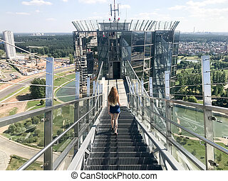 A beautiful girl, a woman with long hair in the hair comes down the metal stairs with a railing on the roof of a glass skyscraper, a tall building with a view of the big city from a height metropolis
