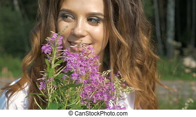 A beautiful girl blows on the seeds of wild flowers that fly in different directions. slow motion