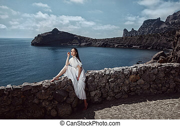 A beautiful girl, bride, in a white dress sits a stone fence, on a cliff against the background of the ocean and mountains.