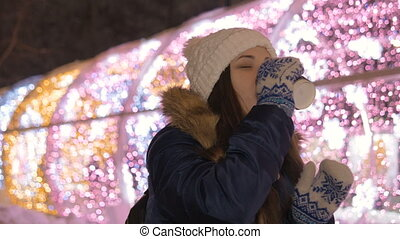 A beautiful girl drinks coffee to keep warm on the street in the winter.