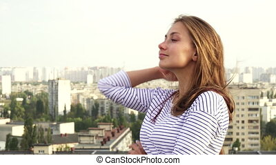 A beautiful girl enjoys seeing from the roof to the city